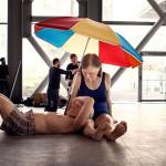 Scultura iper realistica di coppia di anziani sotto un ombrello